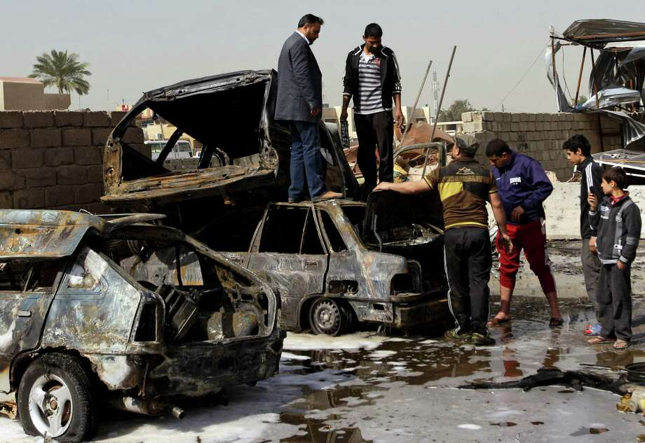 People inspect their destroyed cars at the scene of a car bomb attack in the Ameen neighborhood of eastern Baghdad, Iraq, Sunday. A series of car bombs exploded within minutes of each other as Iraqis were out shopping in and around Baghdad on Sunday, killing and wounding scores of people, police said. Photo: AP
