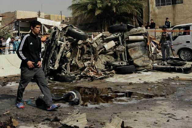 An Iraqi walks past the scene of a car bomb attack in the Ameen neighborhood of eastern Baghdad, Iraq, Sunday. A series of car bombs exploded within minutes of each other as Iraqis were out shopping in and around Baghdad on Sunday, killing and wounding scores of people, police said. Photo: AP