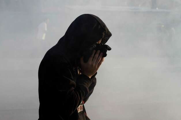 A Bahraini anti-government protester reacts to tear gas fired by riot police during clashes in Daih, Bahrain Saturday. Clashes erupted after the burial ceremony for a 16-year-old boy killed by police fire on Thursday's clashes when Bahraini anti-government protesters headed toward the heavily guarded site of the 2011, pro-democracy uprising. Photo: AP