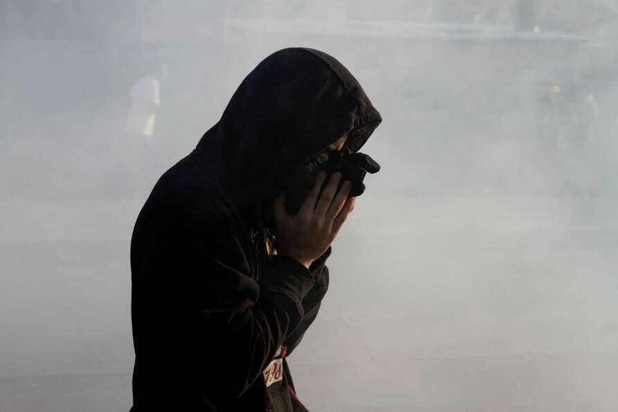 A Bahraini anti-government protester reacts to tear gas fired by riot police during clashes in Daih,