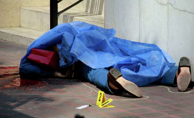 Blood covers the sidewalk next to the body of an unidentified man where police evidence markers lay next to a bullet casing at a crime scene in the Zona Rosa neighborhood of Mexico City, Friday. The shooting occurred in broad daylight in one of Mexico City's tourist hot spots outside a popular restaurant. Photo: AP