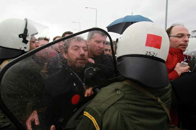 Farmers clash with police during a highway protest near the northern Greek city of Serres, on Thursday. Police used tear gas to disperse protesters and detained three people. Farmers associations have launched a campaign of hour-long highway blockades around Greece, demanding changes to the new tax code and other austerity measures. Photo: AP