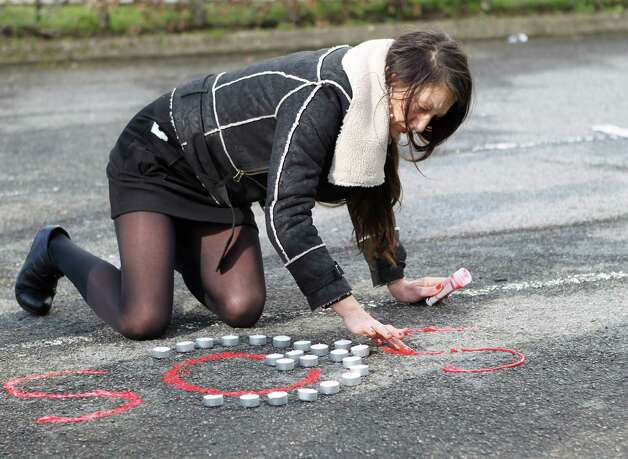 "A woman writes a SOS on the ground in front of an unemployement office in Nantes, western France, Thursday as an homage to an unemployed man who died here Wednesday after setting himself on fire. In a statement, French Work Minister Michel Sapin called the death a ""shocking drama."" It comes as unemployment in France has risen to the highest in over a decade at 10.3%, according to the French statistics agency INSEE. Photo: AP"