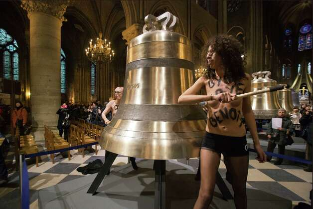 Activists of the Women's Movement FEMEN, sounds one of the bells ordered for the cathedral's 850th birthday, in Notre Dame Cathedral, Paris,  in protest against the Pope Benedict XVI who announced his resignation yesterday,  in Paris, Tuesday. Photo: AP