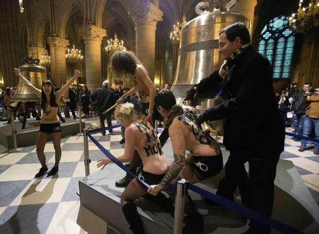 Activists of the Women's Movement FEMEN,  are confronted by security guards as they stand by one of the bells ordered for the cathedral's 850th birthday, in Notre Dame Cathedral, Paris,  in protest against Pope Benedict XVI who announced his resignation yesterday,  in Paris, Tuesday. Photo: AP