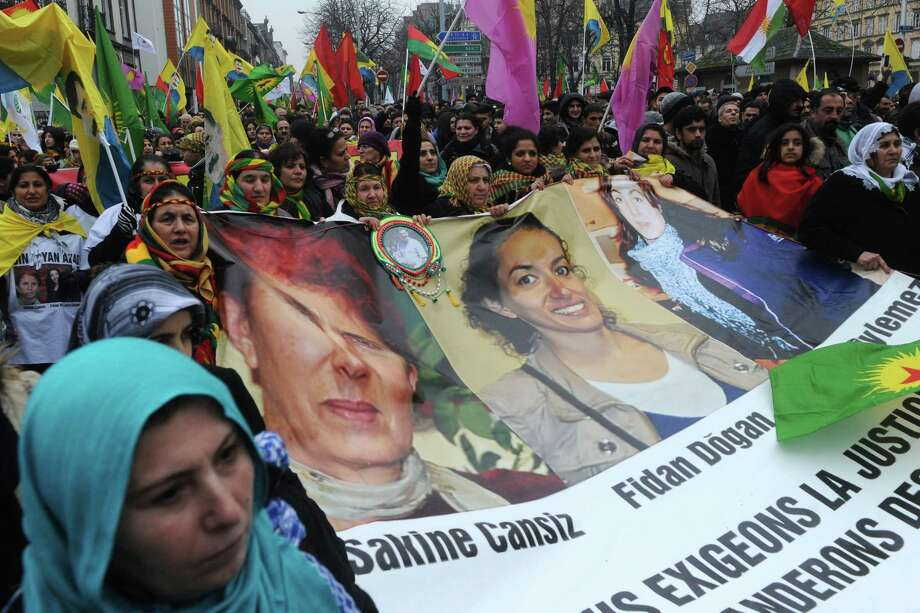 Kurds march with flags and a banner showing pictures of the three PKK (Kurdistan Workers Party) activists killed in Paris last month to show support for  them and to their leader Abdullah Ocalan, imprisoned in Turkey, during a protest in Strasbourg, eastern France, Saturday. Kurds from France, Germany and Belgium gathered for a march through Strasbourg. Photo: AP