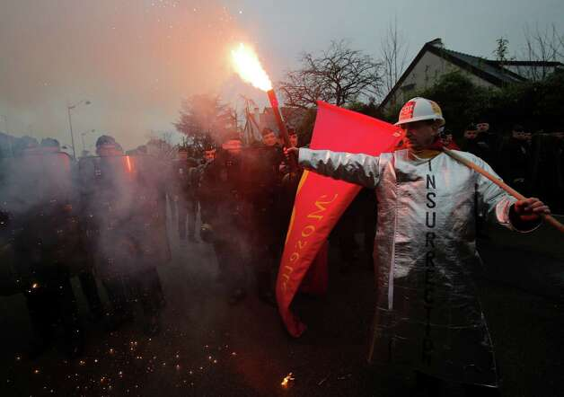 A worker of tire manufacturer Goodyear holds a flare as he faces French riot police during a demonstration in front the Goodyear headquarters, in Reuil Malmaison, outside Paris, Tuesday. U.S. tire maker Goodyear confirmed in January to close a French plant near the northern city of Amiens, which would lead to the layoff of 1,173 jobs. Photo: AP