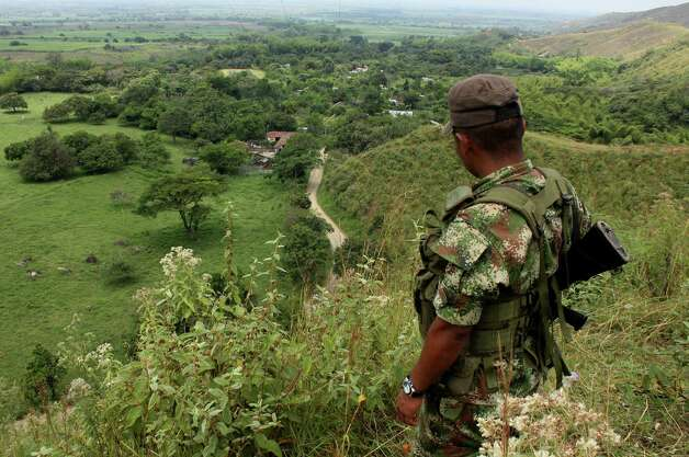 A Revolutionary Armed Forces of Colombia, FARC, rebel stands guard on a hill before the release of two hostages in Montealegre, Colombia, Friday. FARC rebels released Friday, police officers Cristian Camilo Yate, 21, and Victor Alfonso Gonzalez, 26, seized last month. The FARC currently is pursuing peace talks with Colombian government representatives in Cuba. The rebel group declared a two-month unilateral cease-fire when the formal peace talks in Havana began, but that cease-fire lapsed on Jan. 20. Photo: AP
