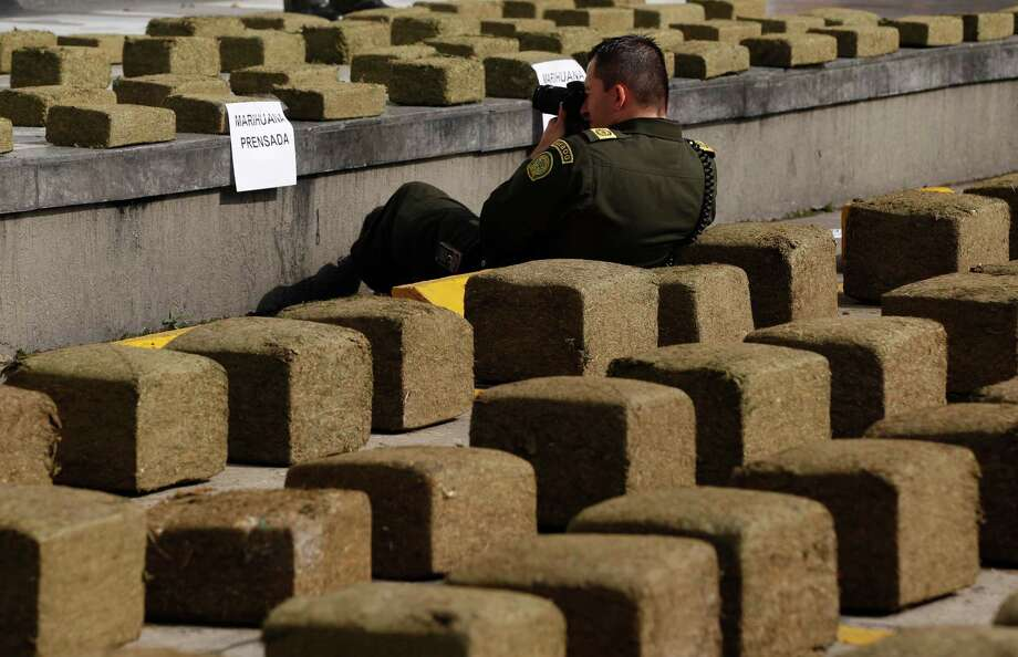 A police officer documents packages of seized marijuana during a media presentation in the parking lot of the metropolitan police headquarter in Bogota, Colombia, Wednesday. Police said they found 3 tons of marijuana in a truck, the biggest seizure of the drug in the city in a decade. Photo: AP