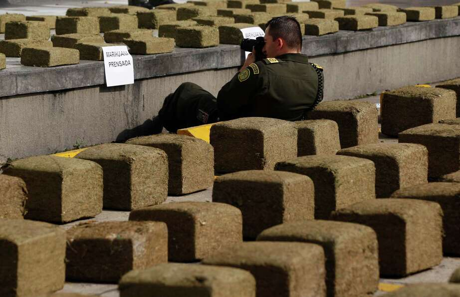 A police officer documents packages of seized marijuana during a media presentation in the parking l