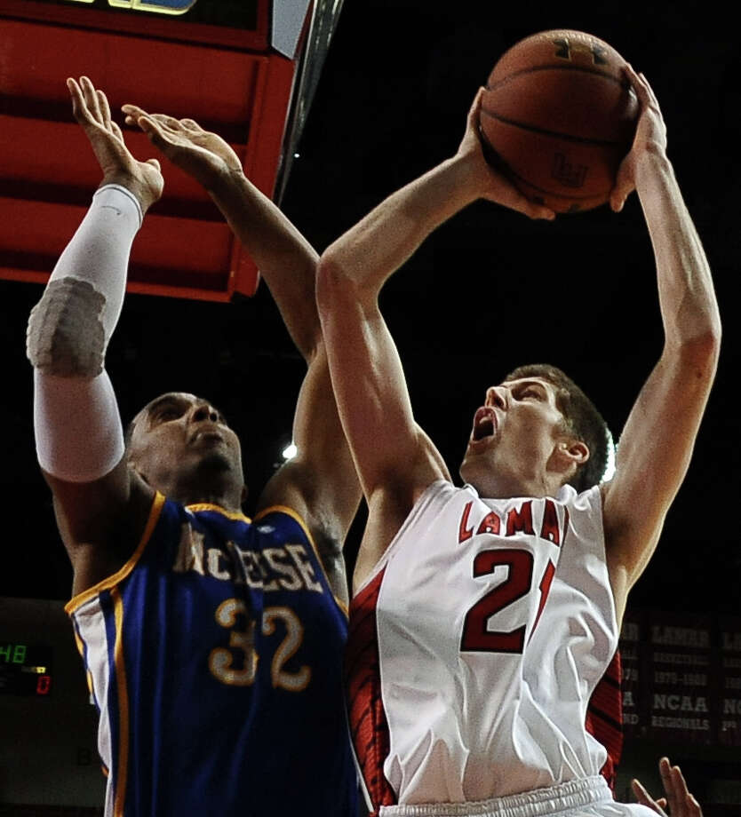 Lamar Cardinal Brennan Doty, #21, puts it up for two against McNeese Cowboy Desharick Guidry, #32, during the Lamar University Cardinals mens basketball game against the McNeese State Cowboys at the Montagne Center on Saturday, February 16, 2013.   Photo taken: Randy Edwards/The Enterprise