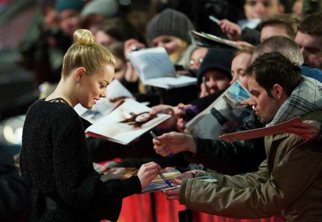 Actress Emma Stone signs autographs as she arrives for the screening of the film The Croods at the 63rd edition of the Berlinale, International Film Festival in Berlin, Friday, Feb. 15, 2013. Photo: AP