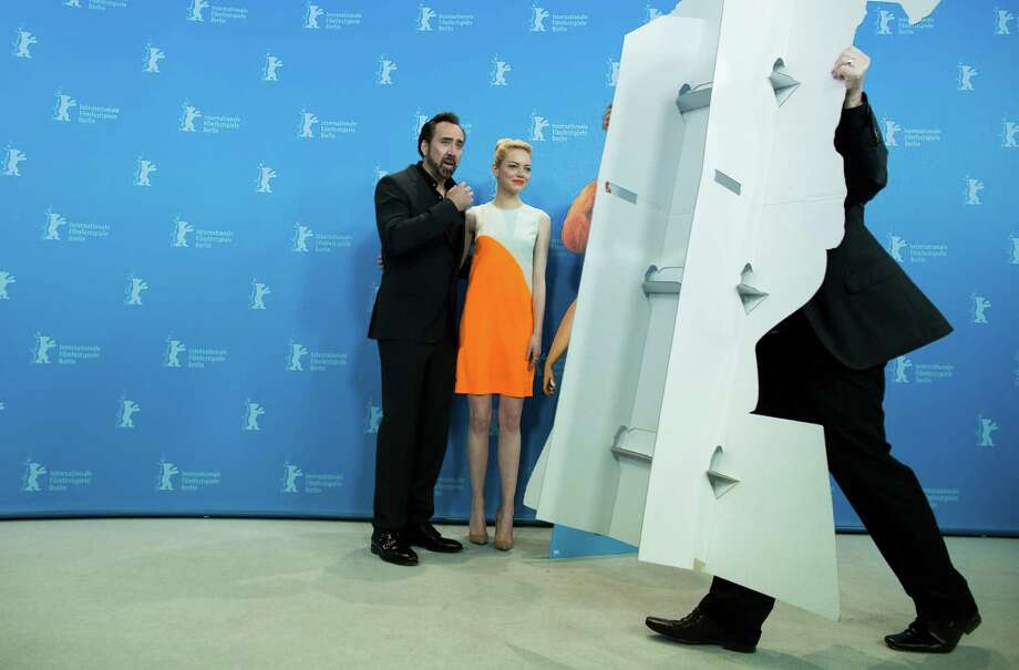 A worker removes a cardboard cut out of the characters in the film as actors Nicholas Cage and Emma Stone pose for photographers at the photo call for the film The Croods at the 63rd edition of the Berlinale, International Film Festival in Berlin, Friday, Feb. 15, 2013. Photo: AP
