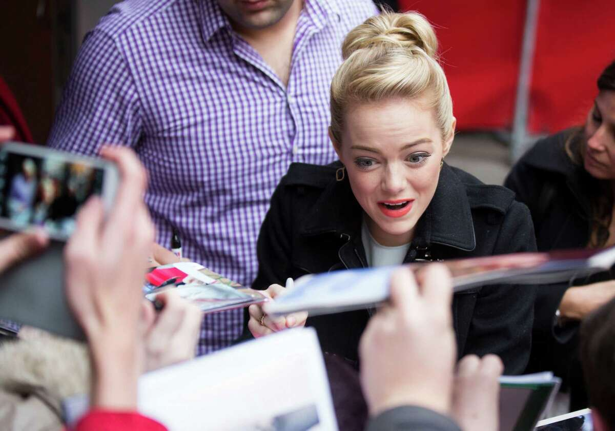 Actress Emma Stone signs autographs as he arrives for the photo call of the film The Croods at the 63rd edition of the Berlinale, International Film Festival in Berlin, Friday, Feb. 15, 2013.
