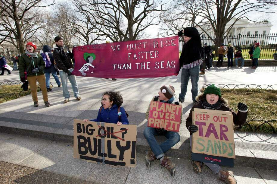 "Katherine Saltzman, from front left to right, Daniel Leibovic, and Lola Katan Kourako, cheer protestors marching in front of the White House in Washington during a rally calling on President Barack Obama to reject the Keystone XL oil pipeline from Canada, as well as act to limit carbon pollution from power plants and ""move beyond"" coal and natural gas, Sunday, Feb. 17, 2013. (AP Photo/Manuel Balce Ceneta) Photo: Manuel Balce Ceneta, Associated Press / AP"