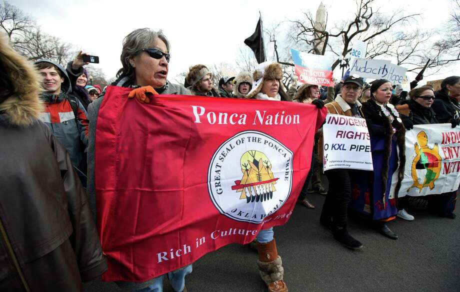 "Missy Crow, front left, of the Ponca Nation of Oklahoma, joins protestors during march from the National Mall to the White House in Washington calling on President Barack Obama to reject the Keystone XL oil pipeline from Canada, as well as act to limit carbon pollution from power plants and ""move beyond"" coal and natural gas, Sunday, Feb. 17, 2013. (AP Photo/Manuel Balce Ceneta) Photo: Manuel Balce Ceneta, Associated Press / AP"