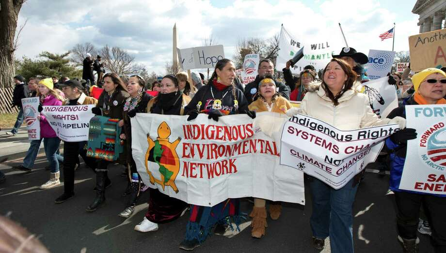 "Native Americans match with other protestors from the National Mall to the White House in Washington during a rally calling on President Barack Obama to reject the Keystone XL oil pipeline from Canada, as well as act to limit carbon pollution from power plants and ""move beyond"" coal and natural gas, Sunday, Feb. 17, 2013.   (AP Photo/Manuel Balce Ceneta) Photo: Manuel Balce Ceneta, Associated Press / AP"