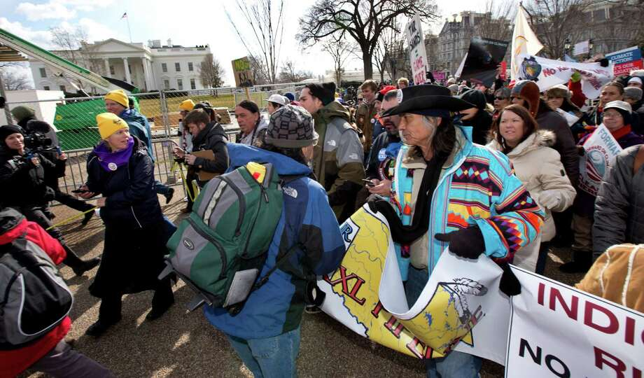 "Native American actor and artist Richard Whitman, right, joins a march in front of the White House in Washington during a rally calling on President Barack Obama to reject the Keystone XL oil pipeline from Canada, as well as act to limit carbon pollution from power plants and ""move beyond"" coal and natural gas, Sunday, Feb. 17, 2013.   (AP Photo/Manuel Balce Ceneta) Photo: Manuel Balce Ceneta, Associated Press / AP"