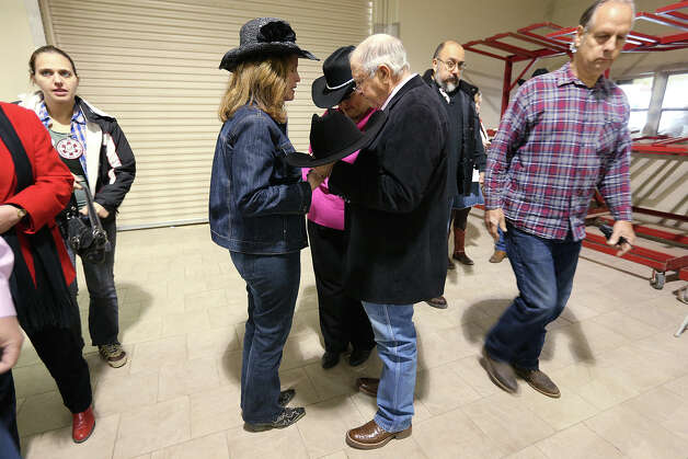 Cowboy Church volunteers Nancy Abbott, center left, and Dawn Milberger pray with guest speaker Weatherford, Texas evangelist J.D. Dunson before Sunday services in the Auction Barn of the San Antonio Stock Show and Rodeo, Feb. 17, 2013. Photo: Jerry Lara, San Antonio Express-News / © 2013 San Antonio Express-News