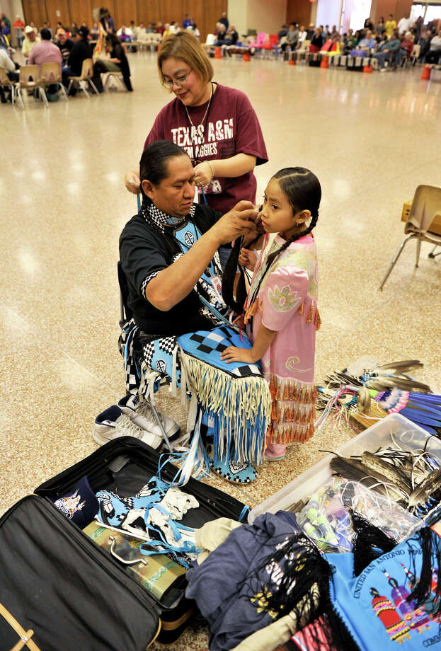 Jennifer Osife braids her husband Calvin's hair as he does the same for their daughter, Dakota, 6,  during the 16th Annual United San Antonio Pow Wow Sunday at the Alzafar Shrine Auditorium.