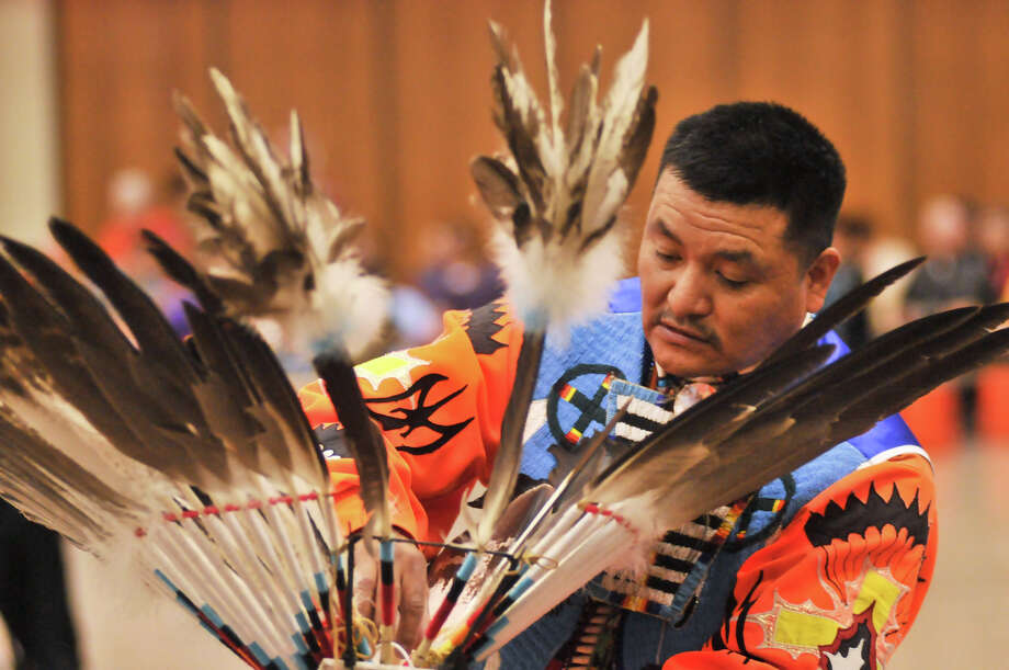 Ryan Sandoval makes adjustments to his head dress during the 16th Annual United San Antonio Pow Wow at the Alzafar Shrine Auditorium Sunday.