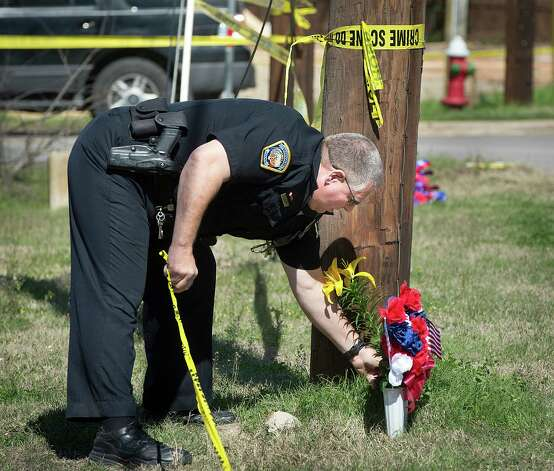 Bryan Police Officer Al Wescoat straightens flowers at a makeshift memorial near a Knights of Columbus Hall, Saturday, Feb. 16, 2013, in Bryan, Texas. Bryan Firefighter Lt. Eric Wallace was killed while battling the Friday night blaze. Three other firefighters were injured and are being treated at burn units in Houston. (AP Photo/Bryan College Station Eagle, Stuart Villanueva) Photo: Stuart Villanueva, MBR / Bryan College Station Eagle