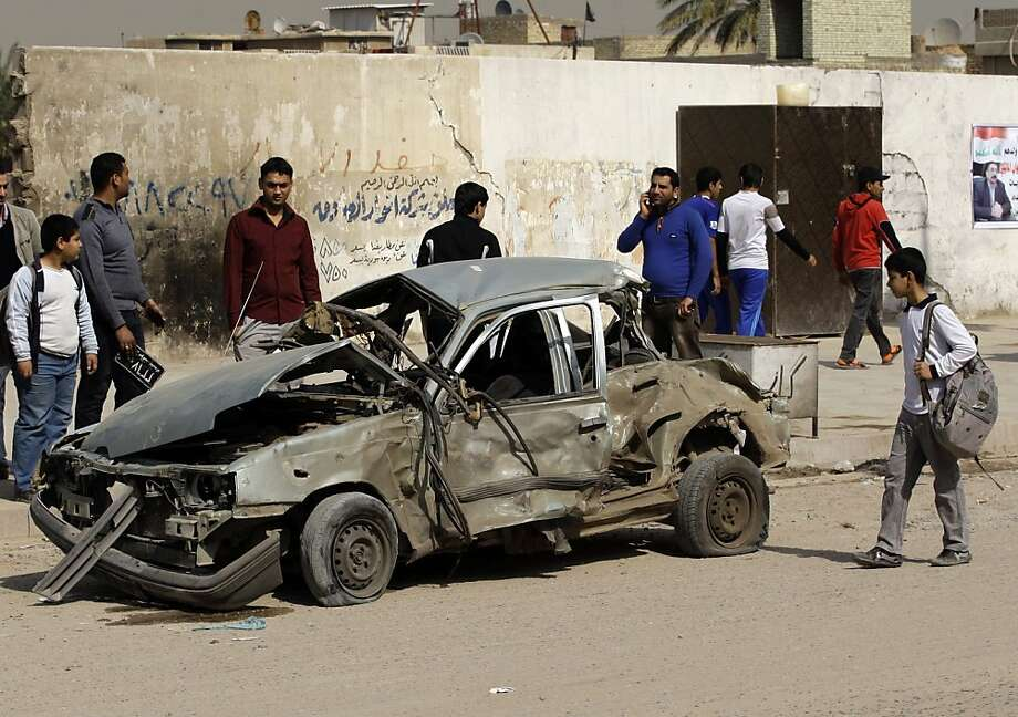 Iraqis check out a car destroyed in a blast in eastern Baghdad. A series of car bombs exploded within minutes of each other near markets in the city, killing and wounding dozens, police say. Photo: Khalid Mohammed, Associated Press