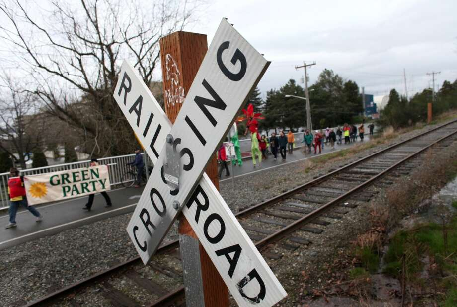 People cross railroad tracks during a protest against proposed coal trains that would pass through Seattle. Opposition to the plan has been fierce, especially in Western Washington.