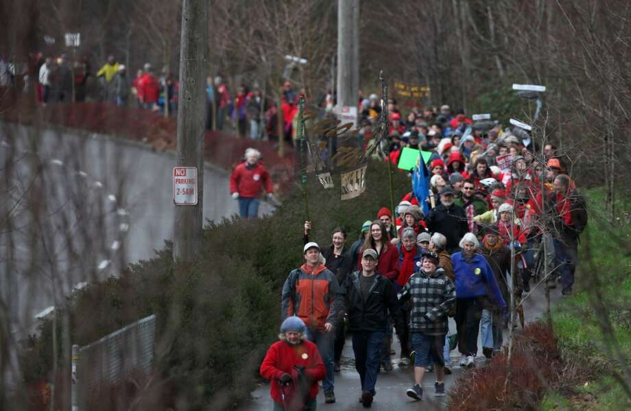 People march along the Burke-GIlman Trail during a protest against proposed coal trains that would pass through Seattle. The trains are part of a proposal to ship coal from the U.S. via rail to ships and eventually to Asia. Opposition to the plan has been fierce, especially in Western Washington.