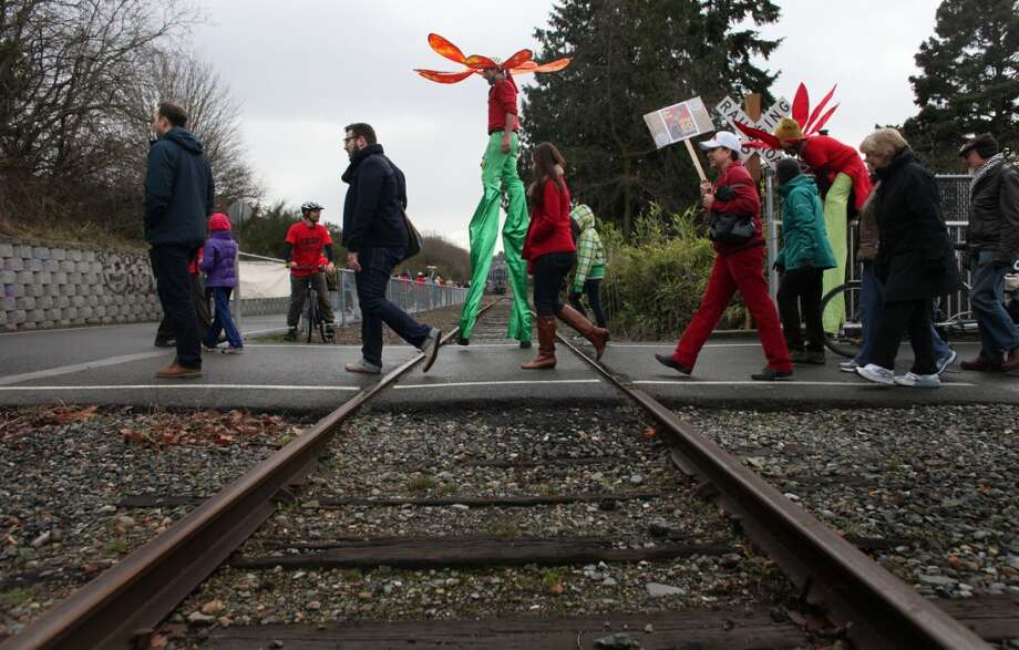 People cross railroad tracks during a protest against proposed coal trains that would pass through Seattle.