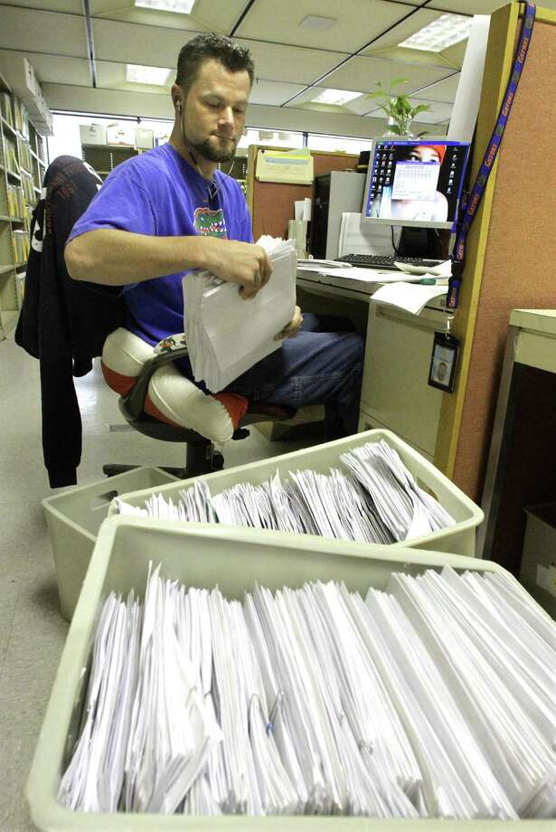 Illinois Department of Revenue office associate Jeff Mumaw processes income tax forms. Photo: Associated Press