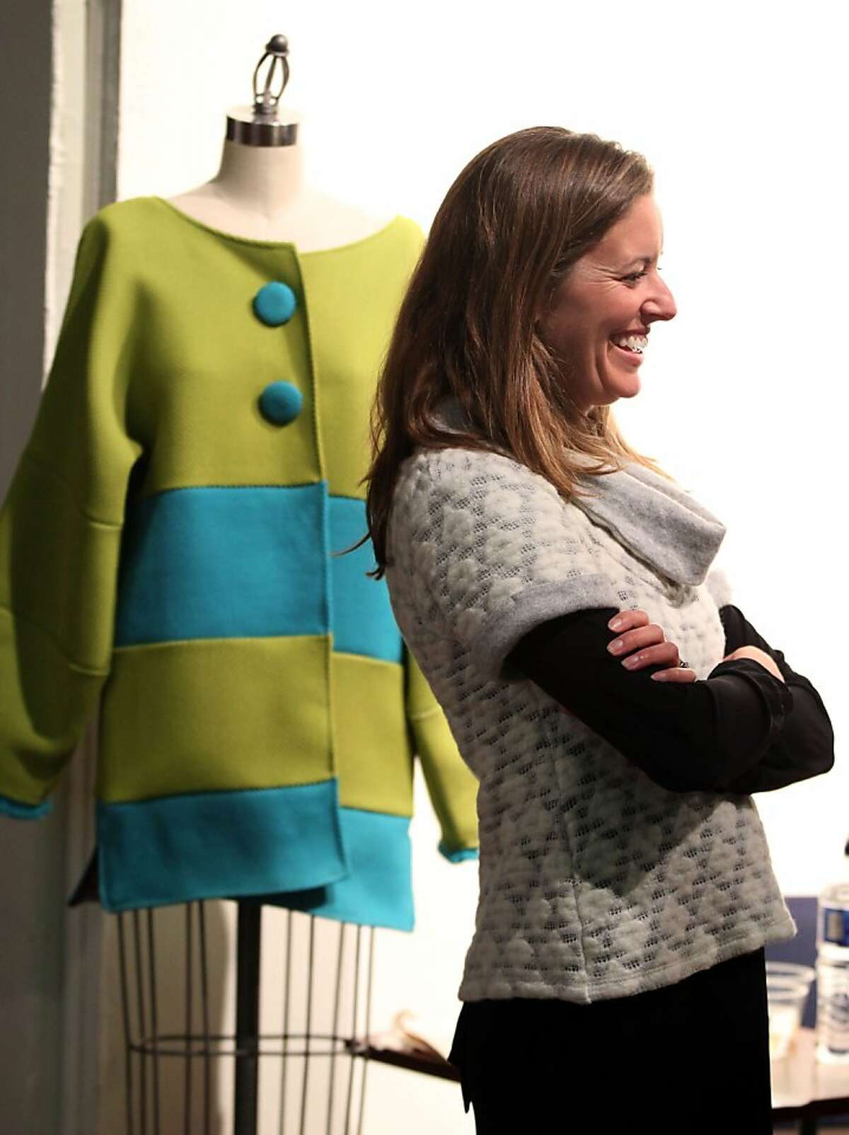 Liz Monteleone models a Dublin Sweeter in front of a Lantern Stove Jacket designed by Kathleen van der Spek of San Francisco at the Philanthropy by Design anniversary party and fundraiser Wednesday, February 13, 2013. In San Francisco Calif.