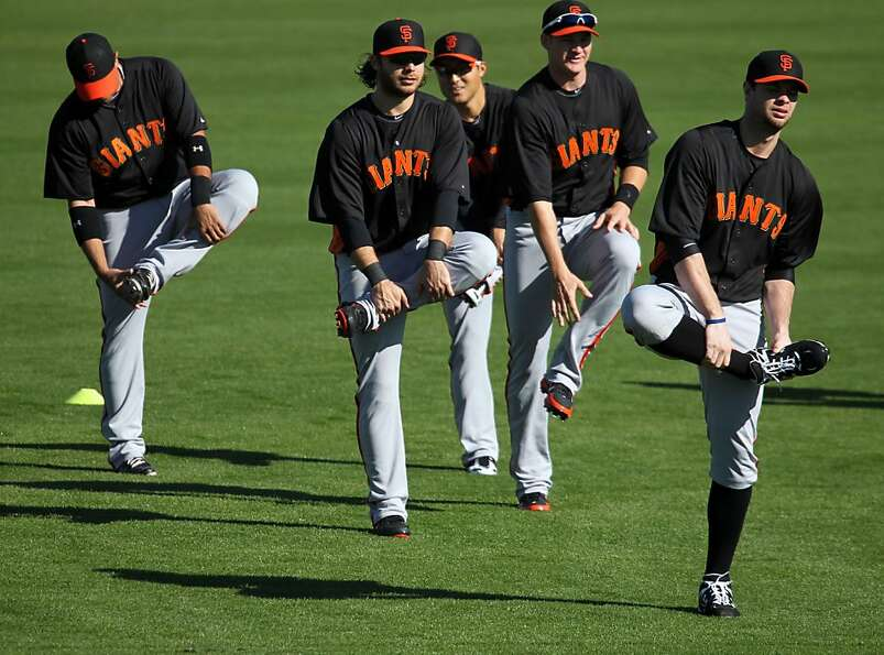 First baseman Brandon Belt (right) leads his teammates through a stretching exercise Saturday in Sco
