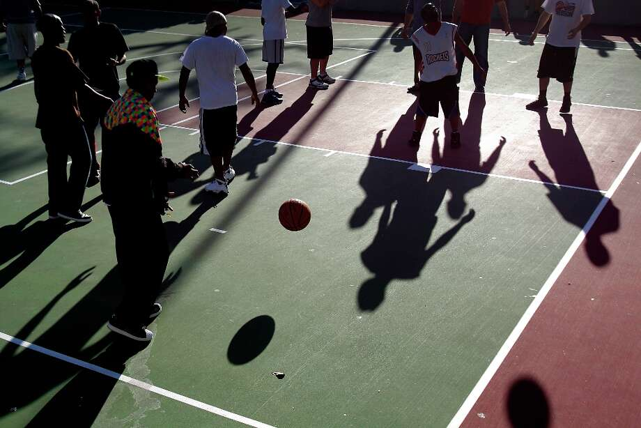 Shadows fall across the court during a pickup basketball game on the Root Memorial Square Basketball Court across the stree from Toyota Center. Photo: Melissa Phillip / © 2013  Houston Chronicle
