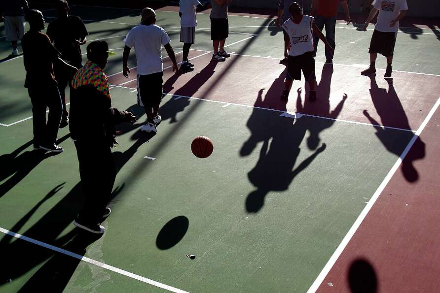 Shadows fall across the court during a pickup basketball game on the Root Memorial Square Basketball