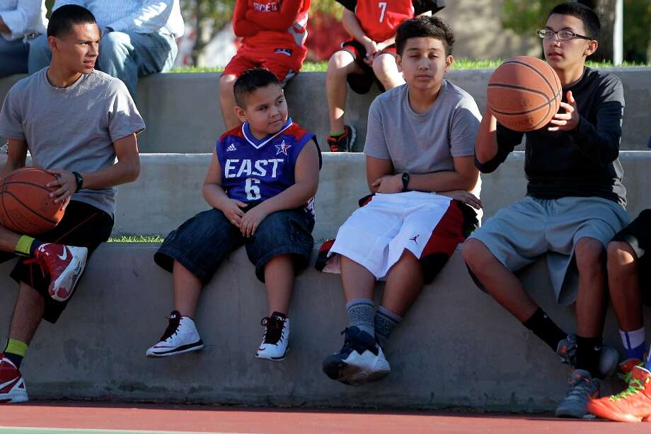 Youngsters watch a pickup basketball on the Root Memorial Square Basketball Court across from Toyota Center. Photo: Melissa Phillip / © 2013  Houston Chronicle