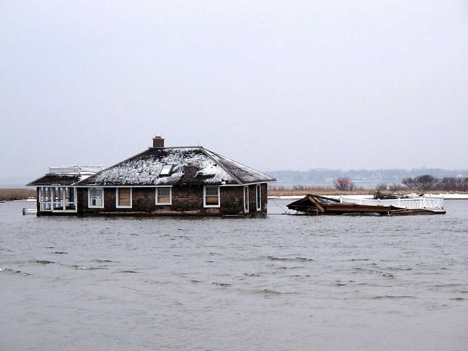 Tons of debris from Superstorm Sandy, such as this house that washed into Barnegat Bay from Mantoloking, N.J., must be removed before the summer swimming and boating seasons begin. Photo: Wayne Parry, Associated Press