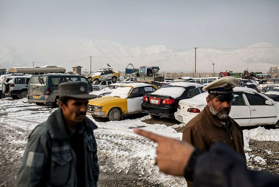 Employees work at the Kabul Traffic Police Parking Lot, known as Car Guantanamo, where police impound cars seized during traffic stops and violations. Photo: Bryan Denton, New York Times