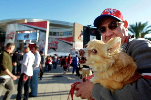 Arthur Salazar of Houston carries his dog, Chiquita, as he takes in the All-Star experience outside the Toyota Center on Sunday. Photo: Melissa Phillip / © 2013  Houston Chronicle