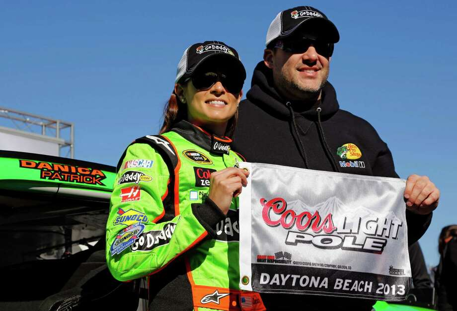 Danica Patrick, left, displays the flag with Tony Stewart after winning the pole during qualifying for the NASCAR Daytona 500 Sprint Cup Series auto race at Daytona International Speedway, Sunday, Feb. 17, 2013, in Daytona Beach, Fla. Patrick became the first woman to secure the top spot for any Sprint Cup race. (AP Photo/Terry Renna) Photo: Terry Renna