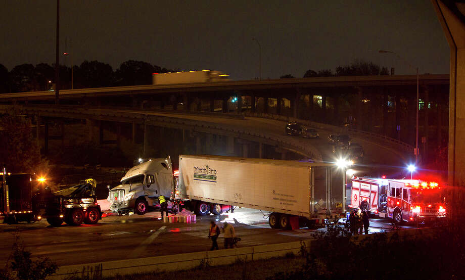 A heavy-duty wrecker prepares to tow an 18-wheeler jackknifed in the westbound lanes of I-10 east of Houston Avenue on Dec. 10. There were four accidents involving big rigs that caused major traffic snarls on that short stretch of road in November and December. Photo: Cody Duty, Staff / © 2012 Houston Chronicle