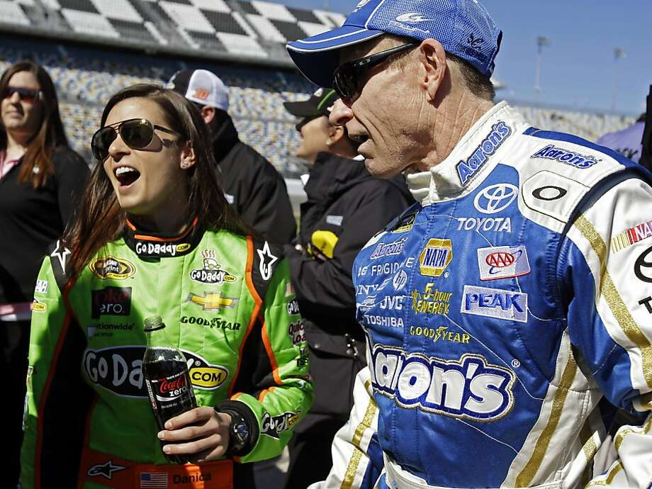 Danica Patrick, flanked by driver Mark Martin, became the first woman to win the pole in a Sprint Cup Series race. Photo: John Raoux, Associated Press