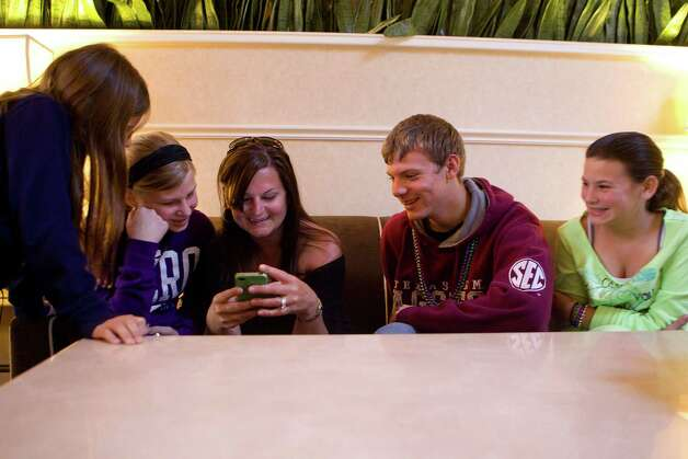 Adrienne Brown, center, of Texas City, looks at vacation pictures with children Elyse, 9, left, Macy, 12, Kenneth, 14, and Amber, 11, while waiting in Mobile, Ala., for husband and father Kenneth to secure a rental car. Photo: Johnny Hanson, Staff / © 2013  Houston Chronicle