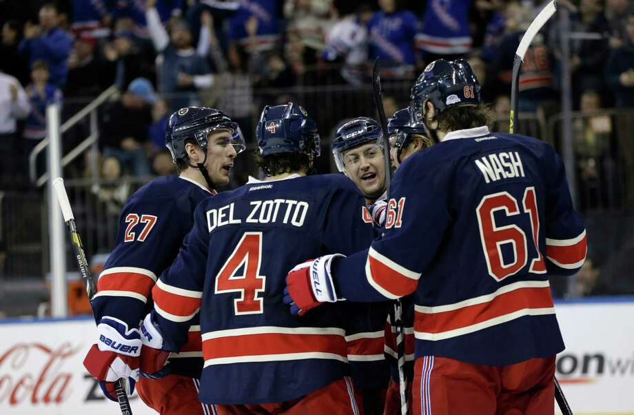 New York Rangers celebrate with left wing Carl Hagelin, second from right, of Sweden, after he scored a goal in the second period of their NHL hockey game agaainst the Washington Capitals at Madison Square Garden in New York, Sunday, Feb. 17, 2013. From left to right, are: defenseman Ryan McDonagh, defenseman Michael Del Zotto, Derek Stepan, Hagelin and left wing Rick Nash. (AP Photo/Kathy Willens) Photo: Kathy Willens