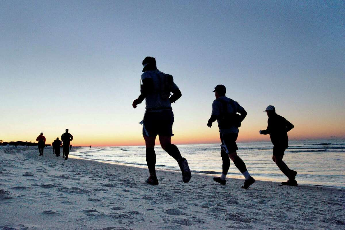 As the sun rises over the Gulf of Mexico in South Walton County, Florida Sunday morning, participants in the 50 kilometer portion of the Destin 50 Beach Ultra competition make their way down the beach near the start of the race at Tops'l Beach Resort in Destin, Fla., Sunday, Feb. 17, 2013.