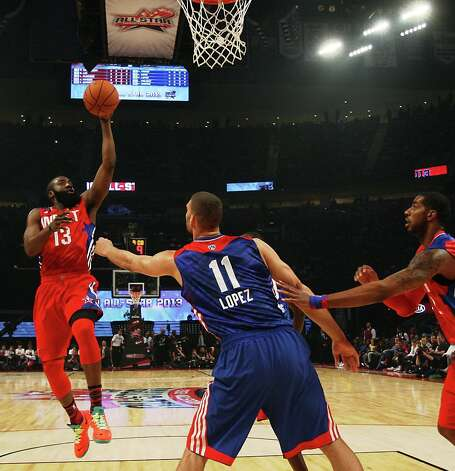 James Harden of the Houston Rockets (13) goes up for a layup over Brook Lopez of the Brooklyn Nets (11) during the first half. Photo: James Nielsen / © 2013  Houston Chronicle