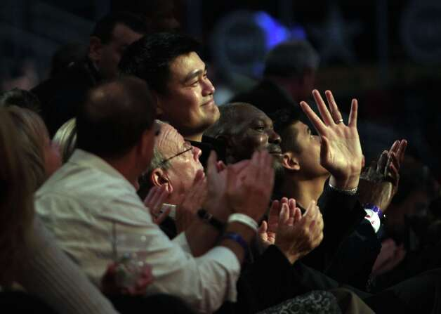 Yao Ming and Hakeem Olajuwon wave to the crowd during the first half. Photo: James Nielsen / © 2013  Houston Chronicle