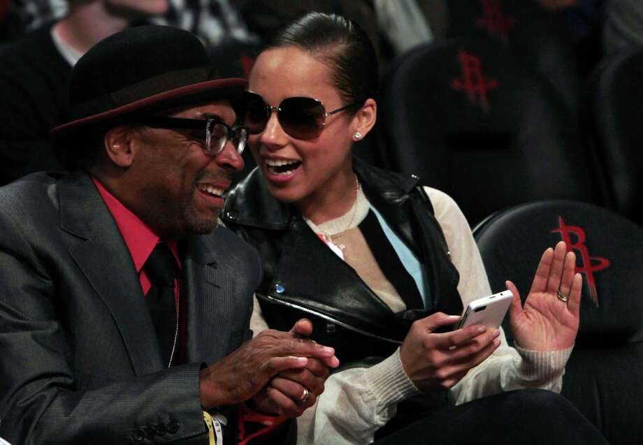 Singer Alicia Keys and director Spike Lee chat in the front row at the Toyota Center on All-Star Saturday Night. Above, Houston's own Beyoncé and husband Jay-Z watch the teams warm up before Sunday night's All-Star Game at Toyota Center. Photo: James Nielsen, Staff / © 2013  Houston Chronicle