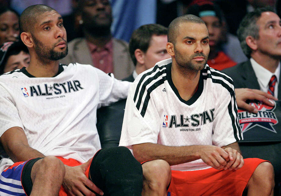 West's Tim Duncan and Tony Parker watch second half action of the 62nd All-Star game against the East from the bench at the Toyota Center Sunday Feb. 17, 2013 in Houston. The West won 143-138. Photo: Edward A. Ornelas, San Antonio Express-News / © 2013 San Antonio Express-News