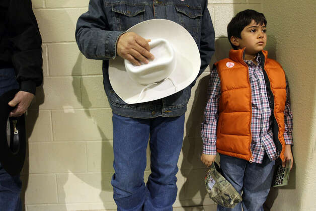 Noah Davila, 8, of Lytle stands with his father, Ernest, during the Cowboy Church service in the auction barn at the San Antonio Stock Show & Rodeo. Nearly 1,000 people gathered for the service. Photo: Photos By Jerry Lara / San Antonio Express-News